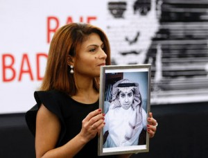 Ensaf Haidar, wife of the jailed Saudi Arabian blogger Raif Badawi, shows a portrait of her husband as he is awarded with the Sakharov Prize, Wednesday Dec, 16, 2015. Haidar says her husband's health is deteriorating. (AP Photo/Christian Lutz).