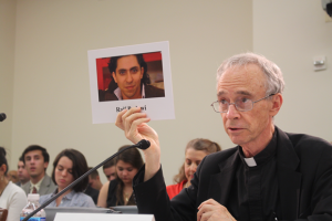 (USCIRF Chair Thomas J. Reese, S.J. holds up a picture of Raif Badawi at a July 2016 Tom Lantos Human Rights Commission hearing on blasphemy laws)
