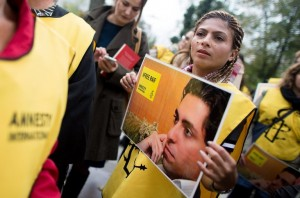 Ensaf Haidar with a picture of her imprisoned husband, Raif Badawi, during a protest outside the Saudi Embassy in Vienna in October. Credit Georg Hochmuth/European Pressphoto Agency