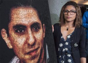 Ensaf Haidar stands next to a poster of a book of articles written by the imprisoned Saudi blogger and Haidar's husband, Raif Badawi, on June 16, 2015 in Montreal. Supporters of jailed Saudi blogger Raif Badawi are sounding the alarm that his flogging could soon resume. THE CANADIAN PRESS/Paul Chiasson